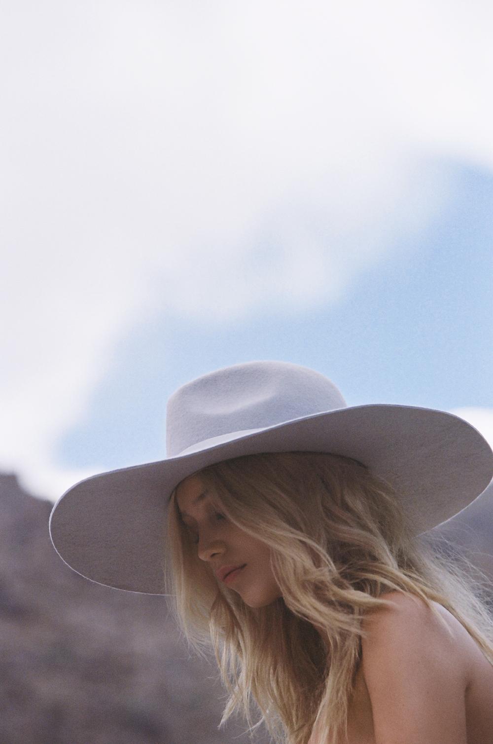 Model wearing lack of color hat